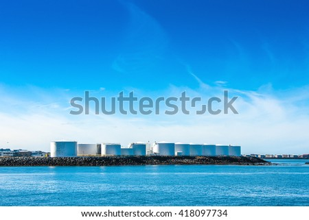 Silo facilities by a blue ocean with blue sky - stock photo