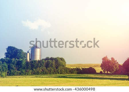 Silo facility on a countryside field in the morning - stock photo