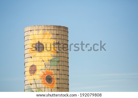 Silo with sunflowers painted on it in green field - stock photo