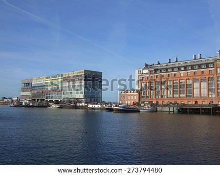 Silodam building and grain silo in Amsterdam port, Netherlands. Silodam, a colorful block containing 157 apartments, was built in 2002. It is now a well known landmark of modern Amsterdam. - stock photo