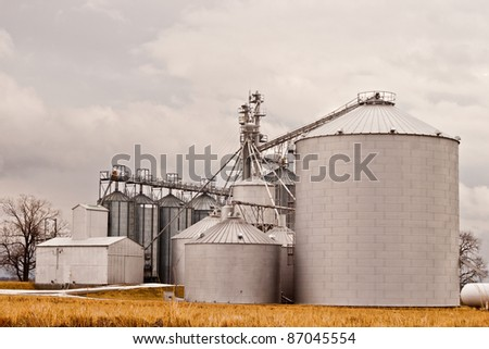Silos on farm against overcast sky - stock photo