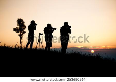 silouette man taking photo of sun rise - stock photo