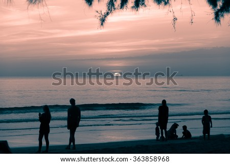 Siluate or Silhouette of people who spent time in the sea sand and beach in the beautiful sky at the sutset. Concept of friendly family.
