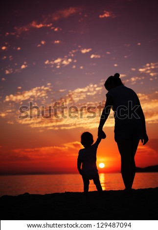 Siluhettes of mother and son by the sea at sunset - stock photo