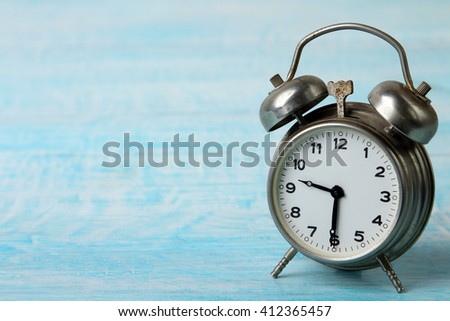 silver alarm clock on blue wooden table