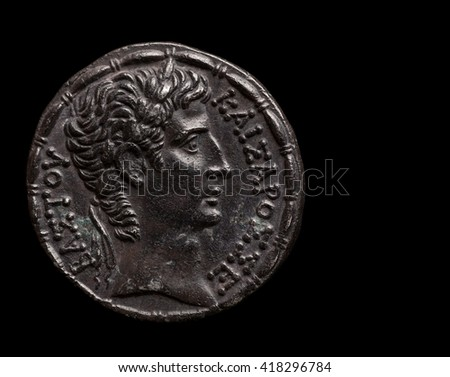 Silver ancient coin of emperor Augustus, copy space, macro shot, isolated on black - stock photo