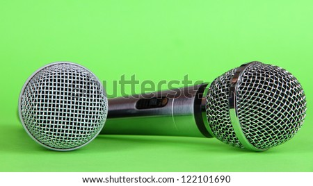Silver and black microphones on green background