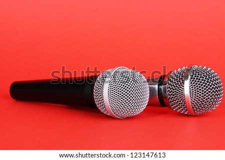 Silver and black microphones on red background