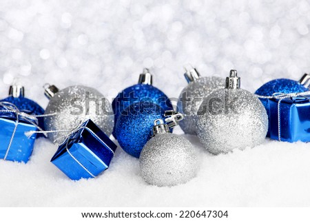 Silver and blue Christmas decorations on snow close-up - stock photo