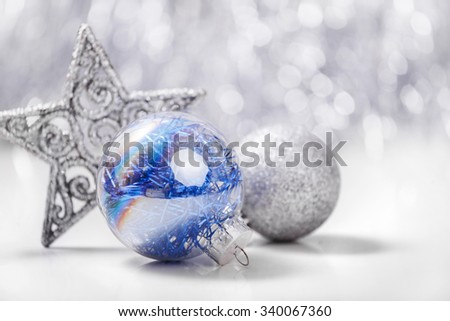 Silver and Blue Christmas ornaments (balls, star) on glitter bokeh background with space for text. Xmas and Happy New Year theme