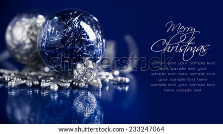 Silver and blue christmas ornaments on dark blue background with space for text. Sample text on solid color, easy to delete. Merry christmas card. Winter holidays. Xmas theme. - stock photo