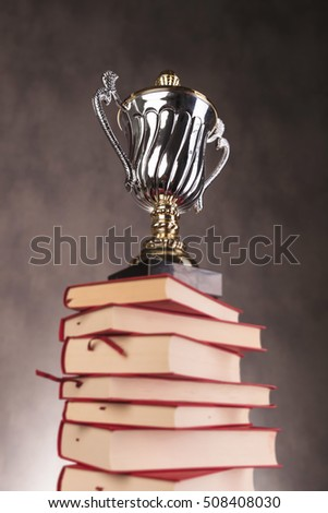 silver and gold trophy cup on top of a pile of books , symbol of success through education