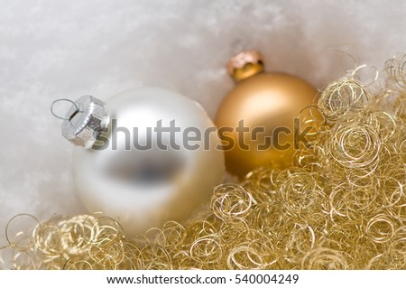 silver and golden christmas tree balls with snow and golden angel hair christmas motif