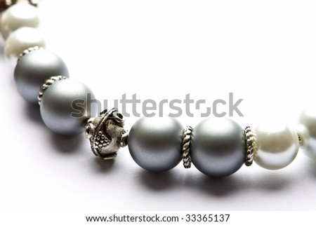 Silver and pearl designer costume jewelery in macro on white background - stock photo