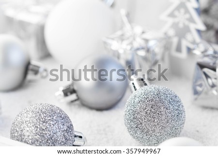 Silver and white christmas baubles on white background.