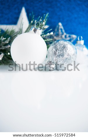 Silver and white christmas ornaments on white and blue bokeh background. Merry christmas card. Winter holiday xmas theme. Happy New Year. Space for text.