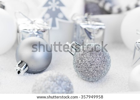 Silver and white christmas ornaments on white background.