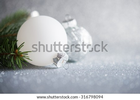 Silver and white xmas ornaments on glitter holiday background. Merry christmas card. Winter holidays. Xmas theme. - stock photo