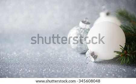 Silver and white xmas ornaments on glitter holiday background. Merry christmas card. Winter theme. Happy New Year. Space for text.