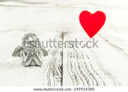 Silver angel and red heart on white wooden background. Valentines Day background - stock photo