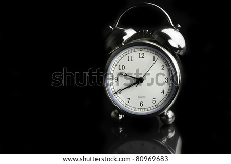 silver antique alarm clock with white dial on a black background - stock photo