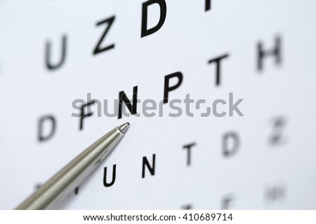 Silver ballpoint pen pointing to letter in eyesight check table. Sight test and correction, excellent vision or optician shop, laser surgery alternative, driver health certificate examination concept - stock photo