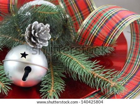 Silver Bell and Ribbon Silver sleigh bell and pine cone, with fresh cut pine. Wide plaid curled ribbon surrounding the red dish. - stock photo