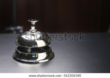 silver bell and the key at the reception in the hotel on a black background