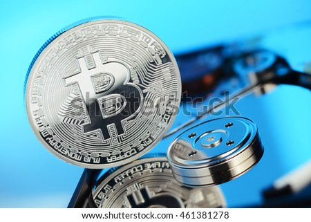 Silver Bitcoin coin on the opened HDD disk. Electronic money, cryptocurrency