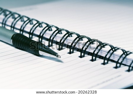 Silver-blue pen lying on opened  notebook - stock photo