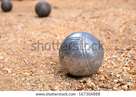 Silver bocce ball on gravel court with two darker bocce balls in the background - stock photo