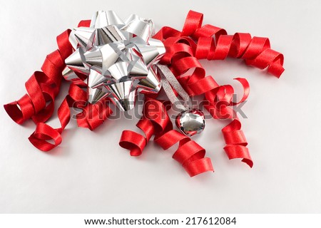 Silver bow, curly ribbon and jingle bell on silver wrapping paper for gift giving themes at Christmas.  - stock photo