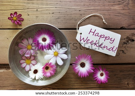 Silver Bowl With Label With English Text Happy Weekend With Purple And White Cosmea Blossoms On Wooden Background Vintage Retro Or Rustic Style - stock photo