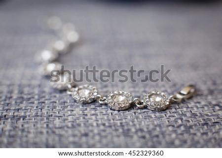 Silver bracelet on gray background - stock photo