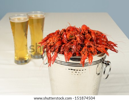 silver bucket of boiled crawfish served with beer - stock photo