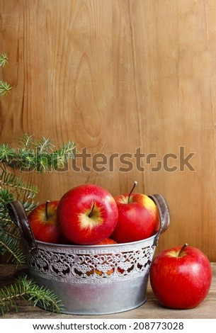 Silver bucket of red apples on wooden table. Copy space
