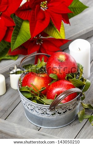 Silver bucket of red ripe apples among candles on rustic wooden table. - stock photo