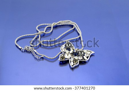 Silver butterfly fashion jewelry with rhinestones on blue mirrorlike background