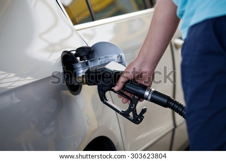 Silver car at gas station being filled with fuel - stock photo