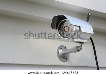 Silver CCTV Camera on the white wall - stock photo