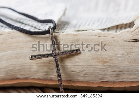 Silver christian cross on bible. Religious concept.