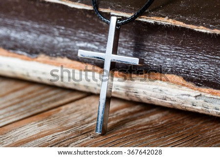 Silver Christian cross on bible. Religious symbols concept.