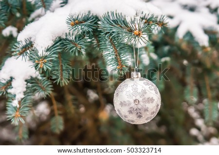 Silver Christmas ball on a snow-covered tree branch, Xmas concept