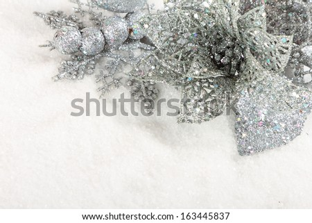 Silver christmas baubles on white snow background