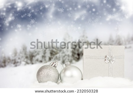 Silver Christmas decorations and gift box in the snow, snow cowered pine trees in the background - stock photo