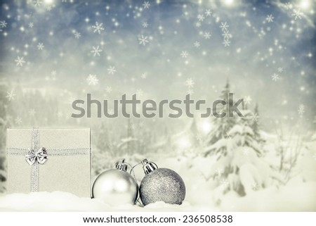 Silver Christmas decorations in the snow, snow cowered pine trees in the background - stock photo