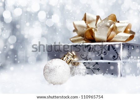 Silver Christmas gift with a huge ornamental golden bow lying with a bauble on a bed of fresh snow with falling snowflakes and copyspace - stock photo