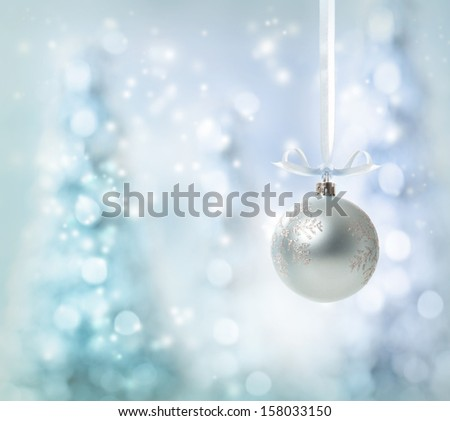Silver Christmas Ornament over glowing tree background - stock photo