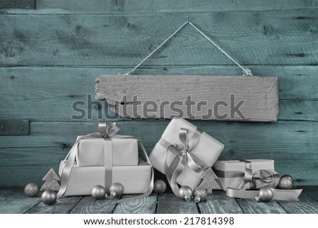 Silver christmas presents on wooden background with a sign for a bonus card. - stock photo