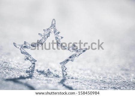 Silver Christmas star on real snow outdoors. Winter holidays concept. Shallow depth of fields - stock photo